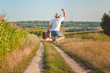 canvas print picture - Backview of excited man with suitcase jumping on country road