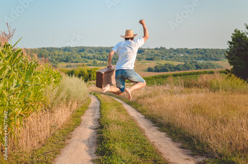 Obraz Backview of excited man with suitcase jumping on country road - fototapety do salonu