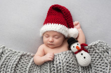 Newborn Baby Boy With Santa Hat And Snowman Plush Toy