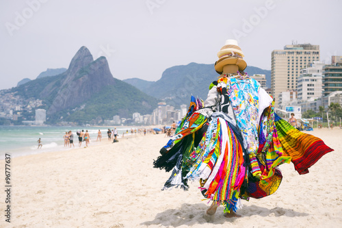 Beach vendor selling brightly colored kanga sarongs carries his merchandise along Ipanema Beach