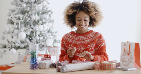 Happy young African woman wrapping presents