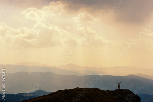 Fotografie, Obraz  Man stands near the cross on top of mountain
