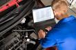 Mechanic Examining Car Engine With Help Of Laptop