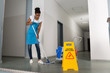 Woman Mopping Corridor
