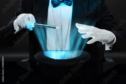 Magician Holding Magic Wand Over Illuminated Hat