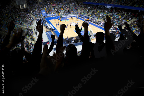 Silhouette of a group of spectators at a professional basketball game cheering for their team