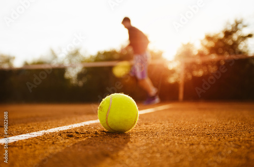 Foto  Tennis ball and silhouette of player on a clay court