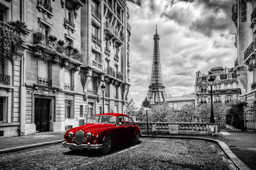 FototapetaArtistic Paris, France. Eiffel Tower seen from the street with red retro limousine car.