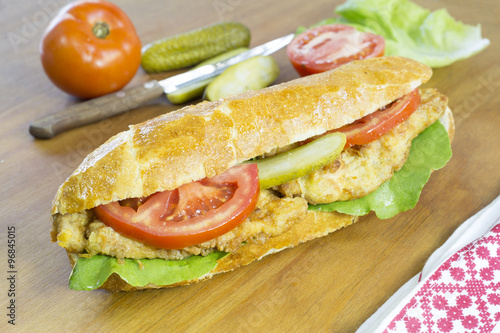 Delicious Chicken Sandwich With Fresh Vegetable on Wooden Table