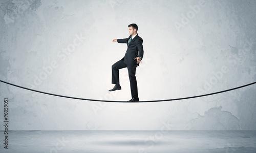 Photo  Sales guy balancing on tight rope