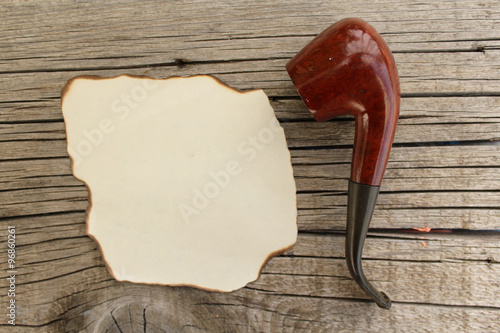 Fotografía  Smoking pipe and empty paper for copy space - hipster fashion - on wooden backgr