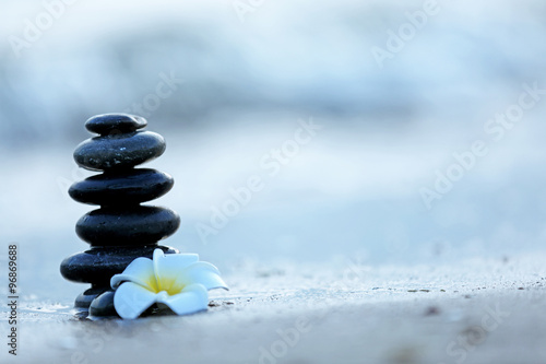 Poster de jardin Zen pierres a sable Spa stones with flower on sea beach outdoors