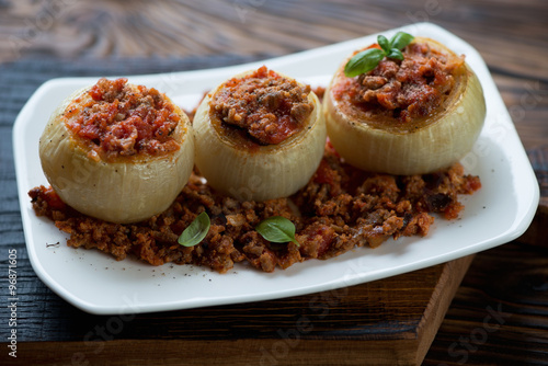 Baked onions stuffed with minced meat on a plate, close-up Wallpaper Mural