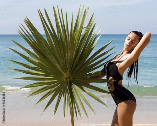 02a77fbef3e Fashion beautiful woman in bikini with palm branch on beach near sea  enjoying sun. Hair up.Tropics.Hot summer day.Sexy girl.Vacation.