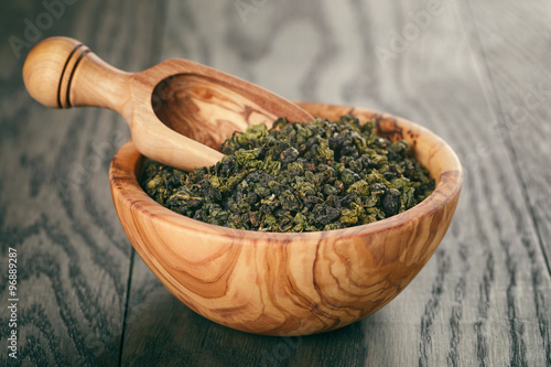 Fotografia  oolong green tea in wood bowl on oak table