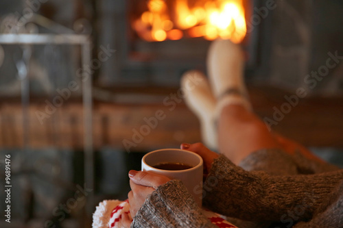 Foto op Plexiglas Wand Woman resting with cup of hot drink near fireplace