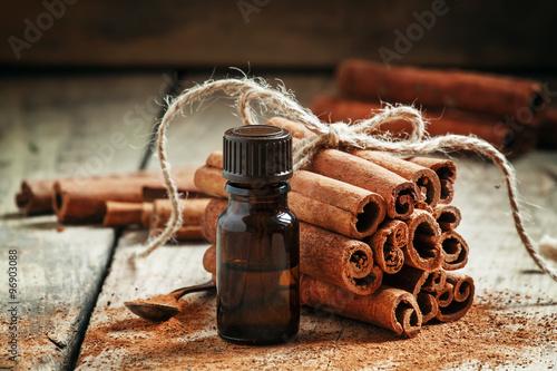 Photo Essential cinnamon oil in a small bottle, ground cinnamon and ci