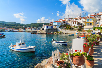 Flowers on shore with fishing boats in Kokkari port, Samos island, Greece