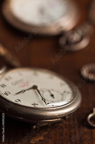 due orologi antichi da taschino in argento,  uno in primo piano, l'altro sfuocat Fototapeta