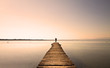Man standing on a small jetty, enjoying the sunset over a lake