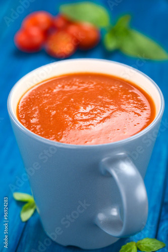 Canvas Prints Tea Fresh homemade tomato soup served in blue cup on blue wood (Selective Focus, Focus one third into the soup)