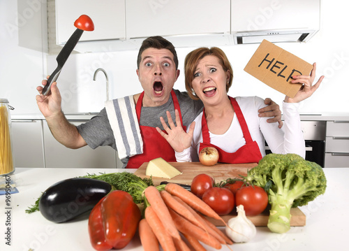 Fotobehang Koken American couple in stress at home kitchen in cooking apron asking for help frustrated