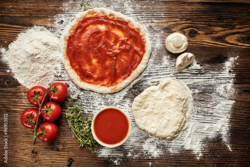 Pizza dough with ingredients on wood Canvas Print
