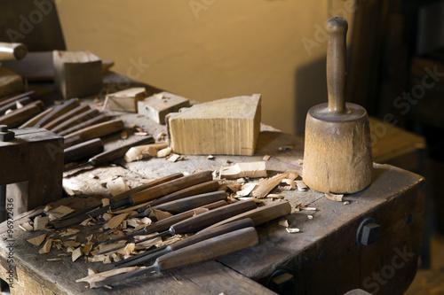 Fotografia, Obraz  Eine Arbeitsbank eines Schnitzlers mit Hammer und Meisseln und Holzresten