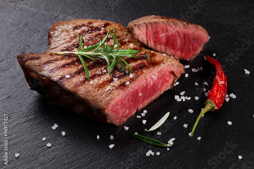 Photo  Grilled beef steak with rosemary, salt and pepper
