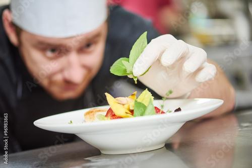 Fotografie, Obraz  male cook decorating dish