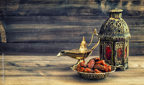 Valokuva  Ramadan lamp and dates on wooden background. Oriental lantern