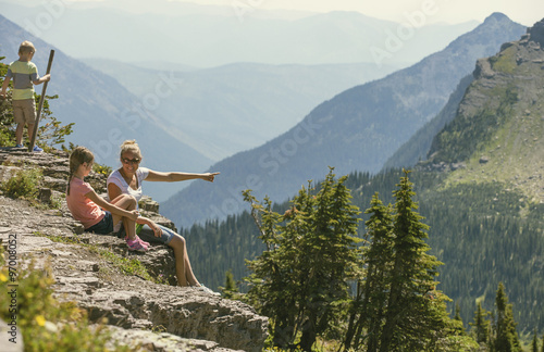 Valokuva  A family sitting together on a rocky ledge looking at a gorgeous view while visi