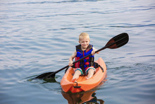 Young Boy Paddling A Kayak On A Beautiful Lake