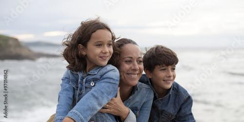 Fotografie, Obraz  Madre, hijo e hija sonriendo mirando al mar