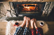canvas print picture - Bare couple feet by the cozy fireplace. Man and Woman relaxes by warm fire with a cup of hot drink and warming up her feet. Close up on feet. Winter and Christmas holidays concept