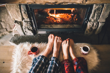 Bare couple feet by the cozy fireplace. Man and Woman relaxes by warm fire with a cup of hot drink and warming up her feet. Close up on feet. Winter and Christmas holidays concept