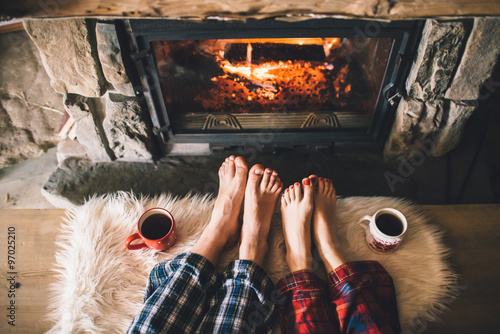 Vászonkép Bare couple feet by the cozy fireplace
