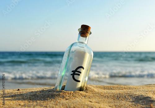 Photo Botella con el símbolo del euro en la orilla de la playa