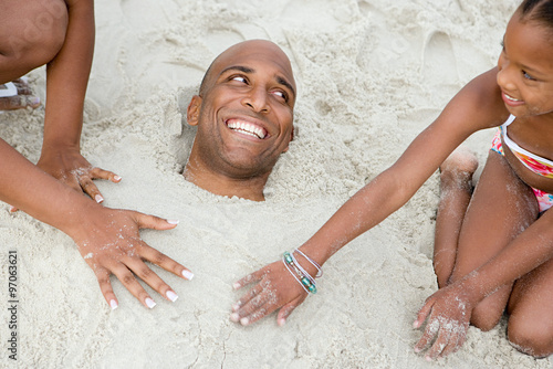 Photo  Family burying father in sand