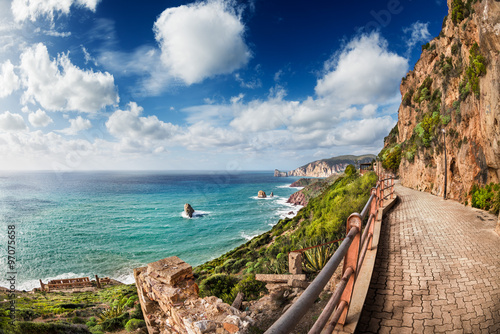 Fotografie, Obraz  Walkway along the coast with high cliffs in the distance with blue sky