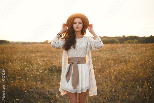 Fotografering  Fashion portrait of beautiful young pretty girl with hippie outfit holding hat outdoors at sunset
