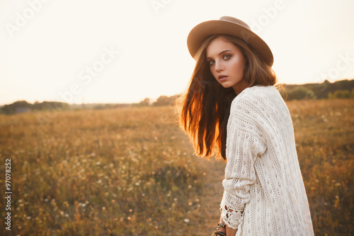 Fotografía  Fashion portrait of beautiful young pretty girl with hippie outfit and hat outdoors at sunset