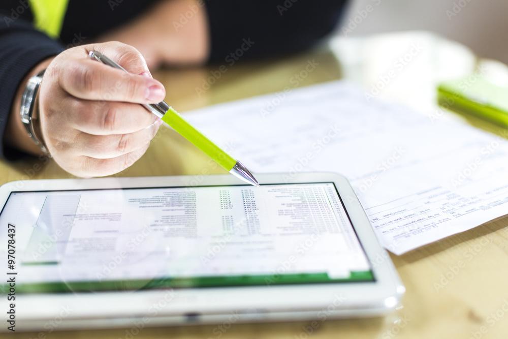 Fototapeta Accounting on a tablet computer, close-up - obraz na płótnie