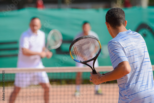 Men playing doubles game of tennis