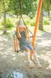 little girl on swing in children's city park