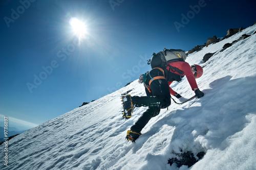 In de dag Alpinisme Bergsteiger klettert die Nordwand des Fuscherkarkopf, Österreich. Kletterer schlägt mit den Steigeisen Stufen ins Eis.