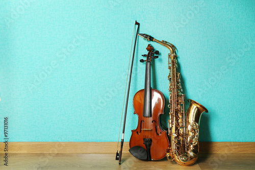 Violin and saxophone on the floor against blue background - 97131016