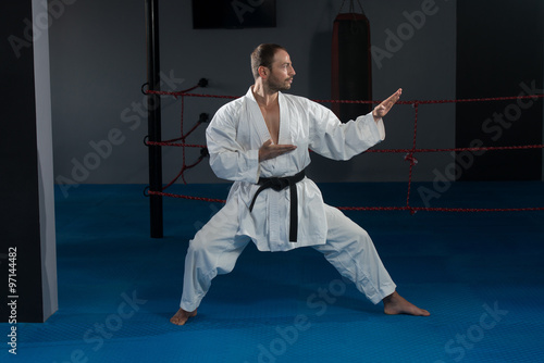 Man In White Kimono And Black Belt Training Karate - 97144482
