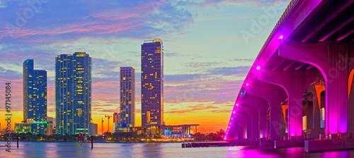 Fototapeta premium Miami na Florydzie o zachodzie słońca, kolorowa panorama oświetlonych budynków i most na grobli Macarthur