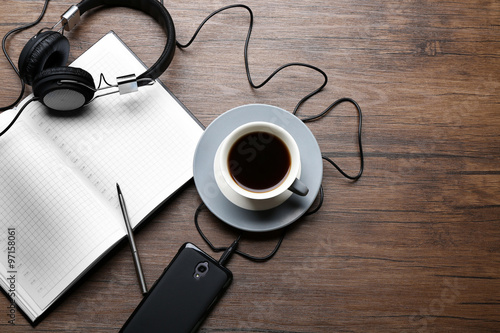Fototapeta Headphones with papers and cup of coffee on wooden table obraz na płótnie